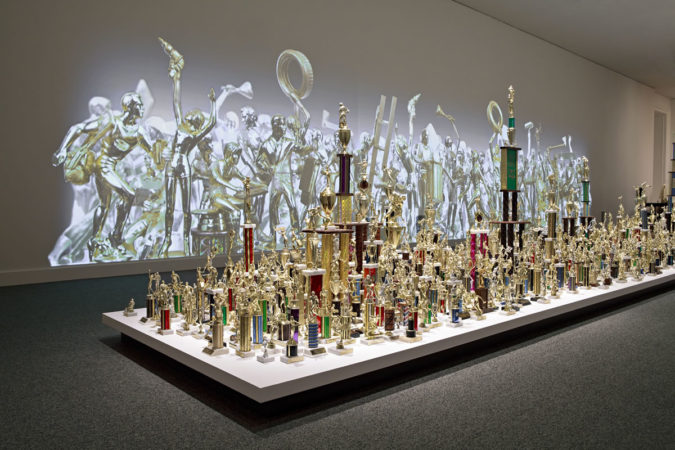 Jean Shin, Everyday Monuments, 2009 Sports trophies, painted cast and sculpted resins, projections Floor Installation: Dimensions variable, approximately 7.33 ft h x 5 ft w x 45 ft d Wall Projection: 9.33 ft h x 42 ft w Commissioned by the Smithsonian American Art Museum, Washington, D.C.